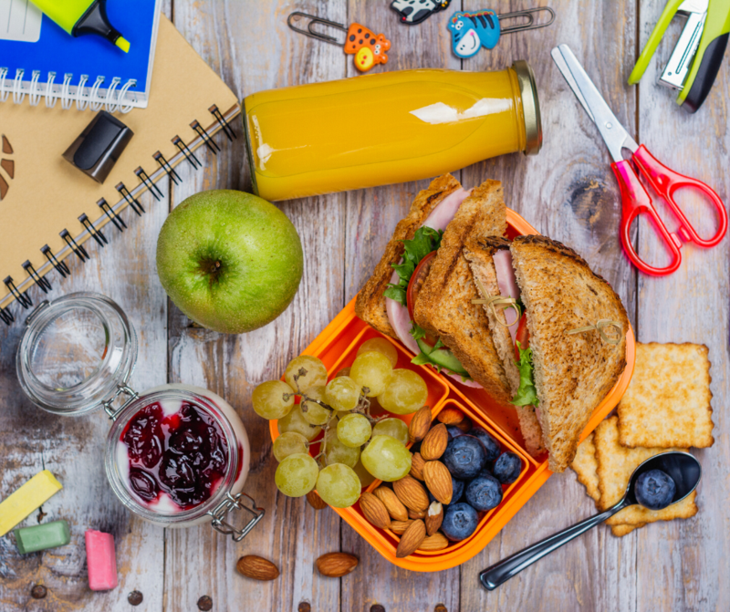 This is a picture of a few school lunch items scattered around the table. A sandwhich, apples and school supplies are scattered.
