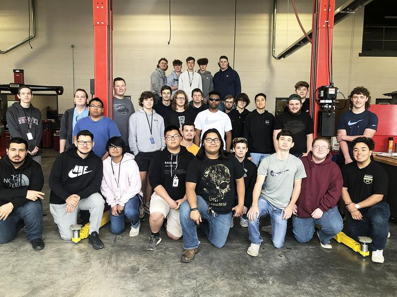 group of automotive technology program students pose together in the WHS auto shop