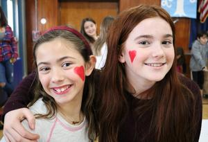 Photo of two Tamaques 5th graders with red hearts painted on their cheeks for Valentine's Day.