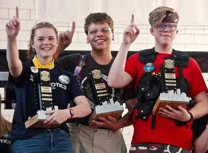 Franklin Regional Senior High School's Courtney Sheridan, Captain, is shown holding Team 4150's winning trophy together with alliance teammates, Benjamin Marcouiller, of Team 2051 from AW Beattie Career Center) and Kyle Berg, of Team 1511 from Rochester Robotics in New York.