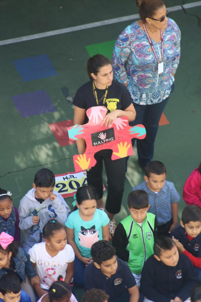 rm 204 teacher holding up puzzle piece against bullying