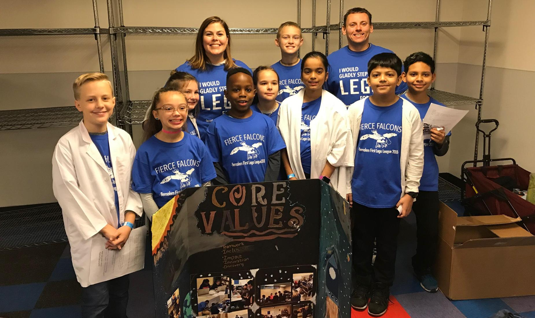 9 boys and girls and their teachers dressed in blue Fierce Falcons shirts ready for their First Lego League Competition