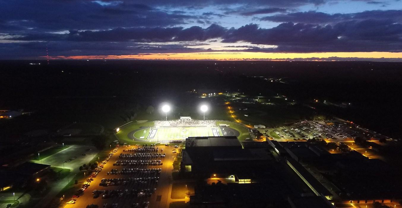 An aerial night view of the TKHS Bob White football stadium shows it all lit up during a game.