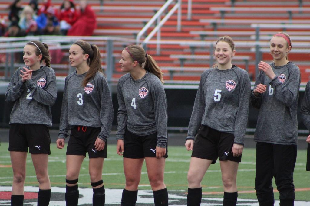 Ladies soccer players standing along the side line