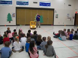 Buster the Bus talks to students in the gym.