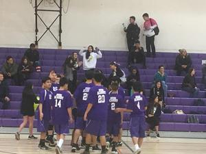 volleyball team in uniform gathering on the volleyball court and people in the stands