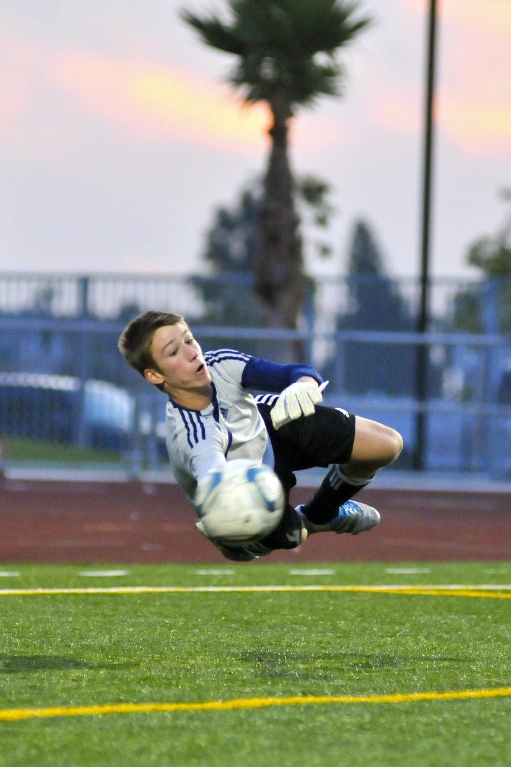 Soccer goalie blocking a shot