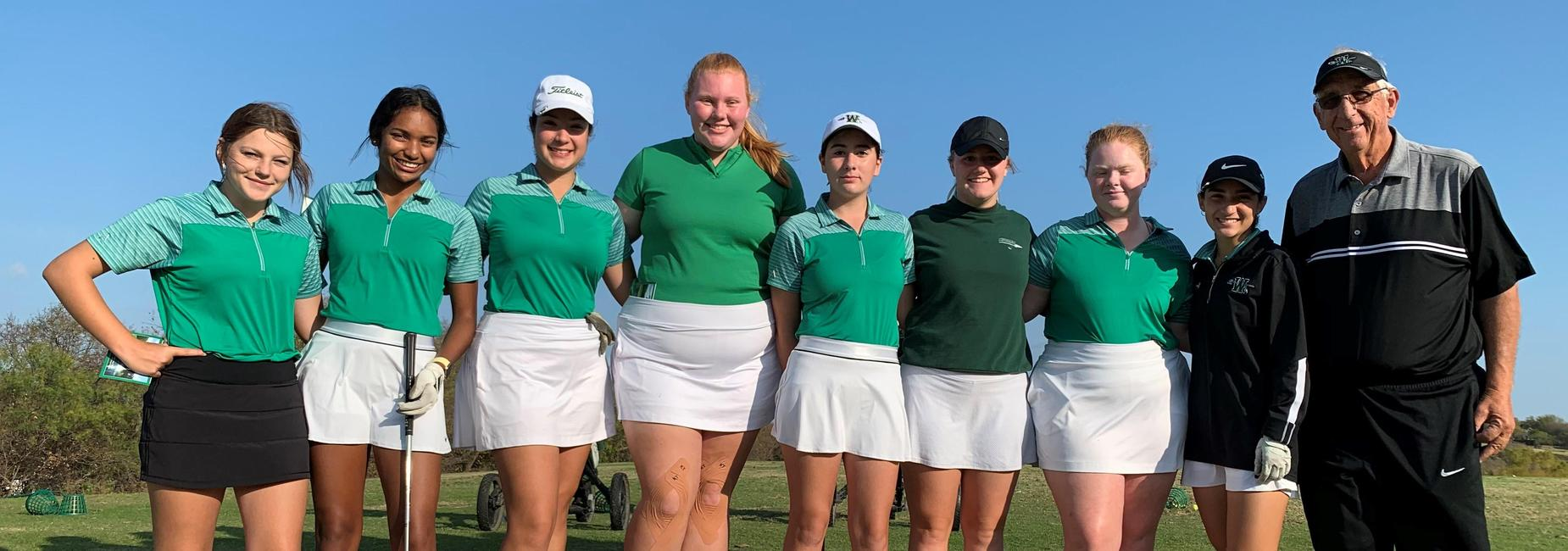 girls golf team and coach on the course