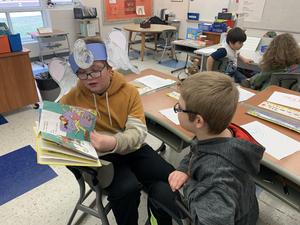 pic of older kids reading to younger