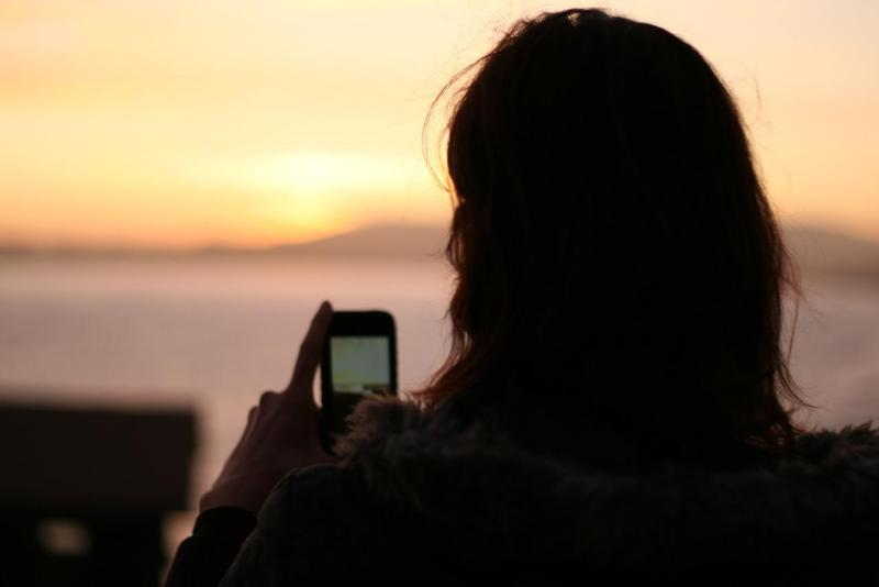 Silhouette of a girl with a smart phone