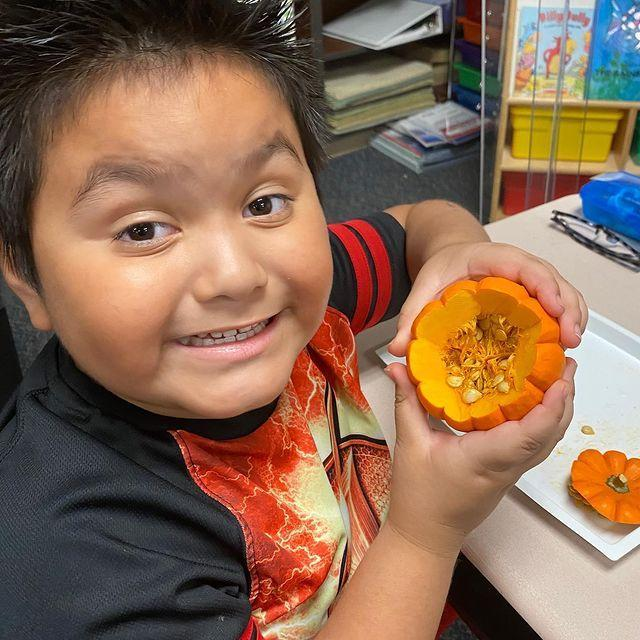 picture of student showing how many seeds are inside his pumpkin