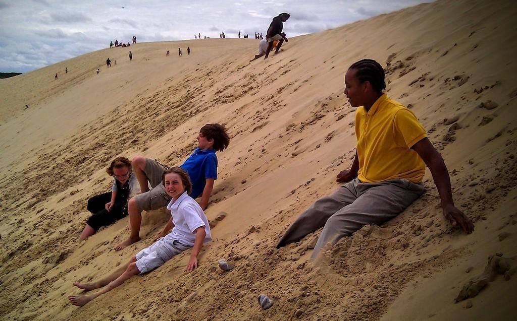 children sitting on sand hill