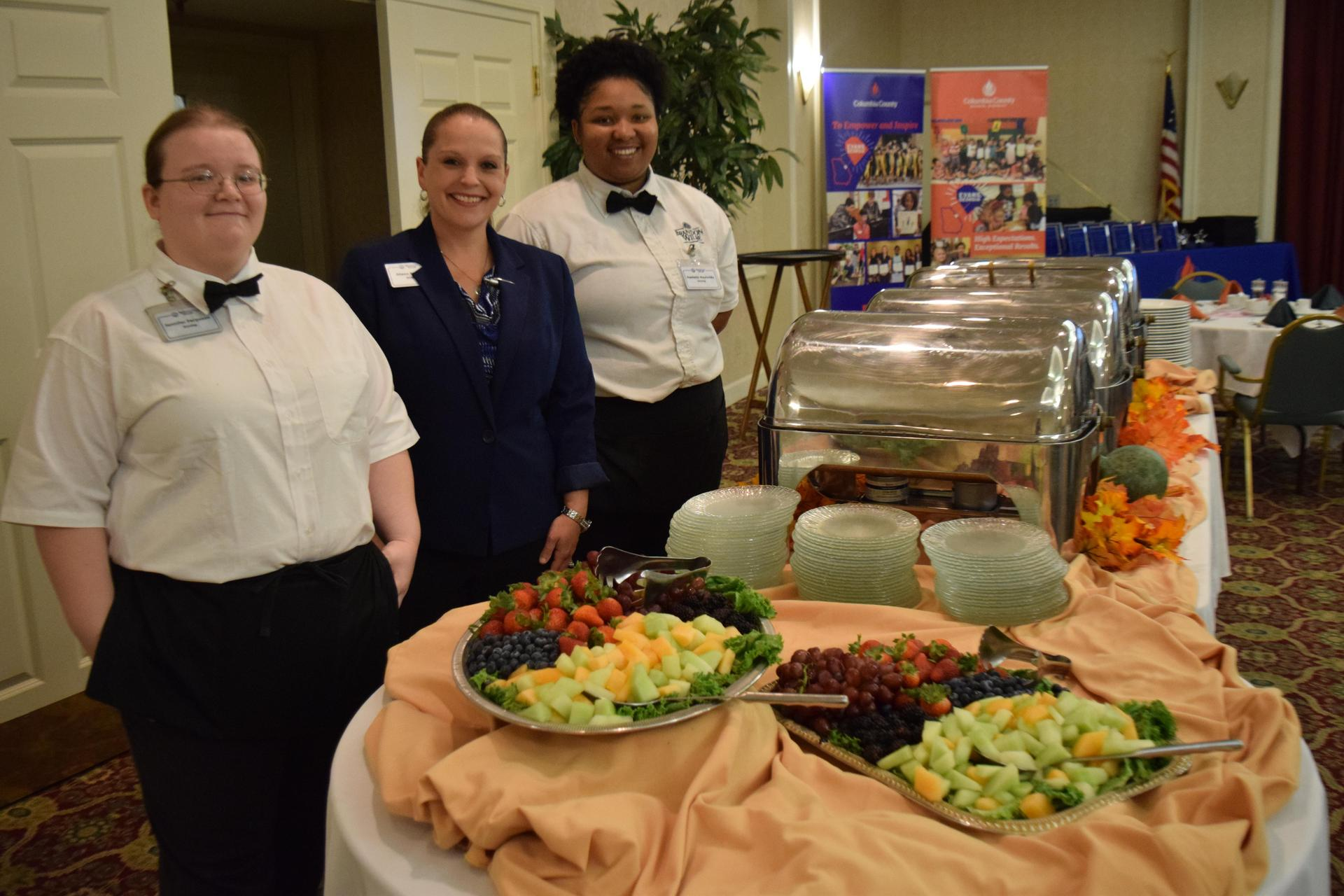 staff smiling next to table of food