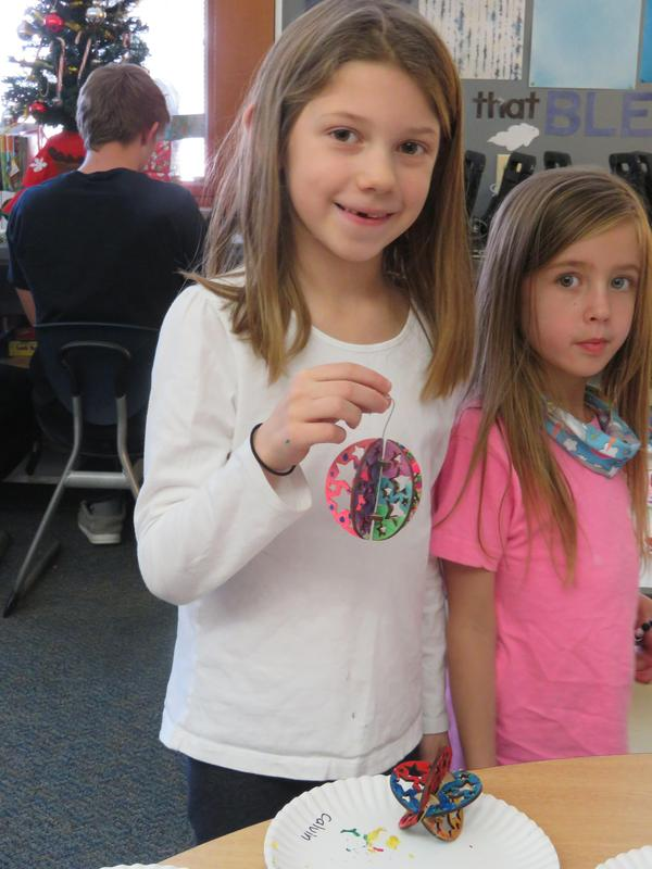 A first grader proudly shows her completed ornament.