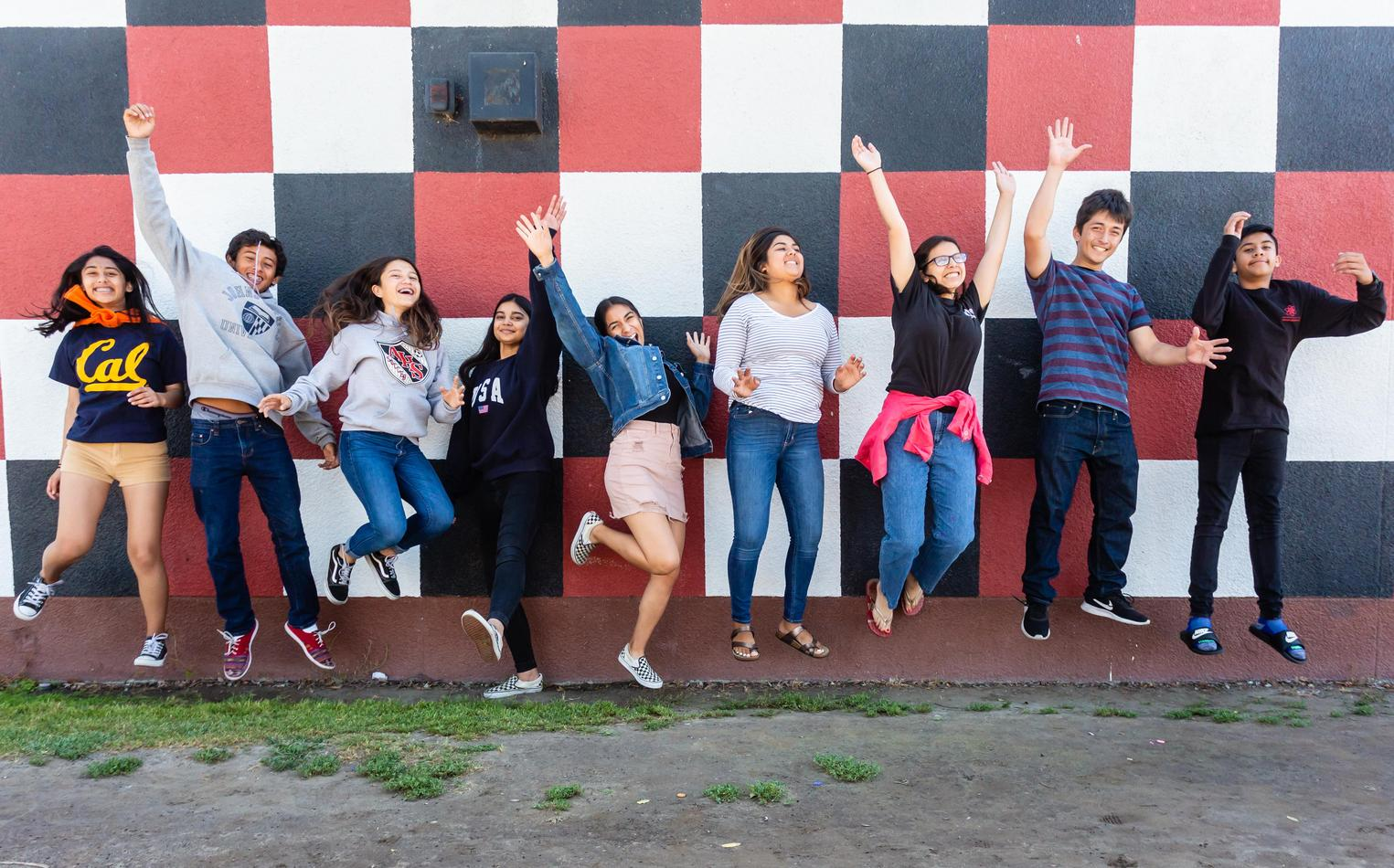 High school students jumping enthusiastically in front of wall mural.