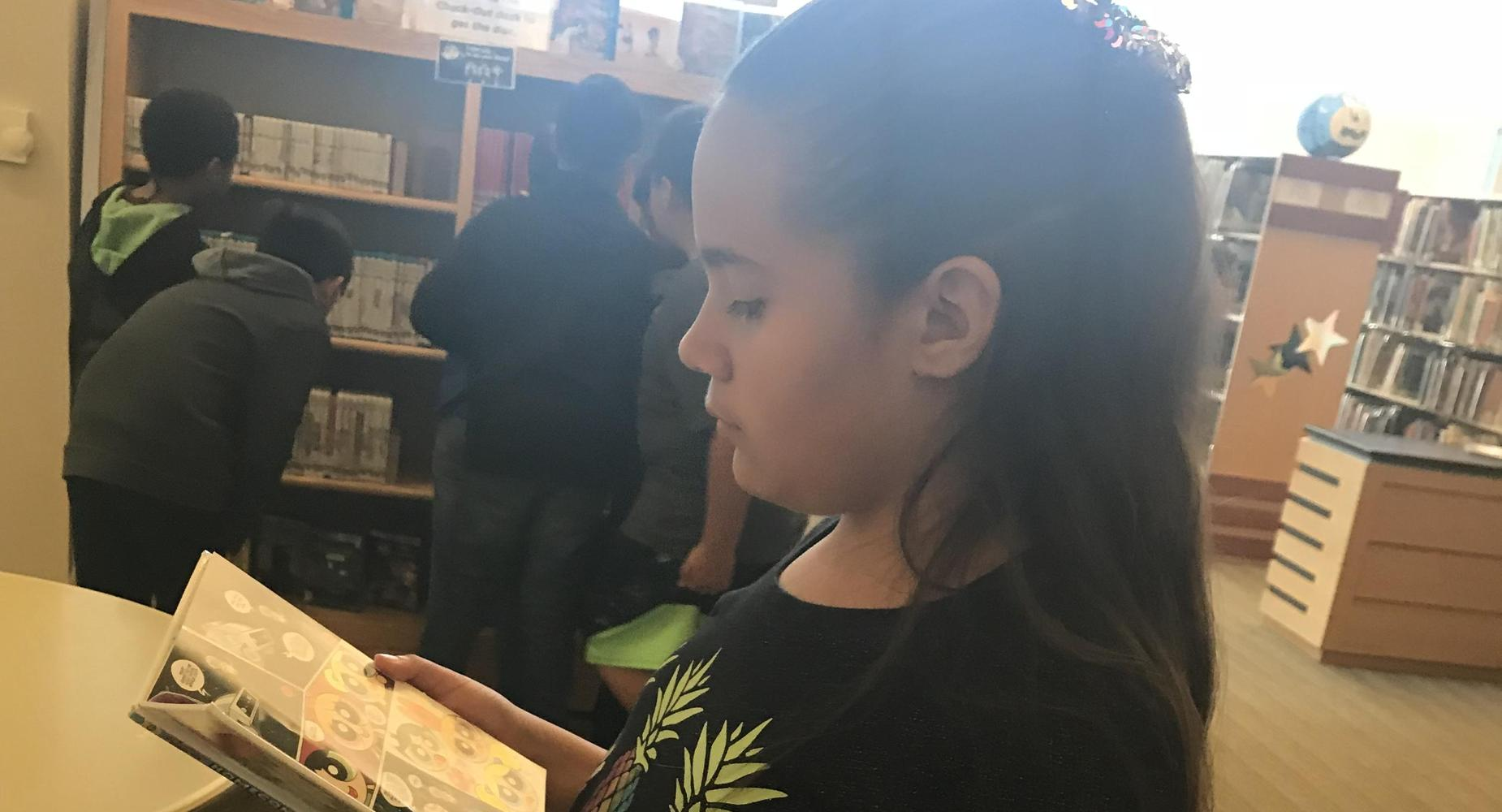 4th Grade girl reading in the library.