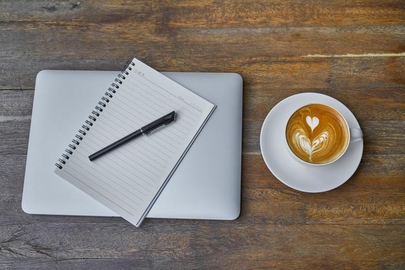 laptop, notebook, and cup of coffee on table