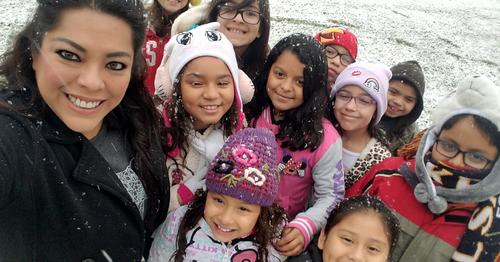 Ms. Ballesteros posing with students on snow day.