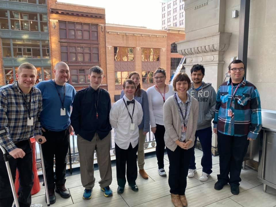 young adults stand in building by window downtown