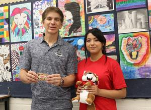 Edinburg North High School art student Brittlee Garcia is pictured holding one of the prizes she was awarded in the Don't mess with Texas® K-12 Art Contest along with her art teacher, Manuel Saenz Jr., who is holding an H-E-B/Central Market gift card.