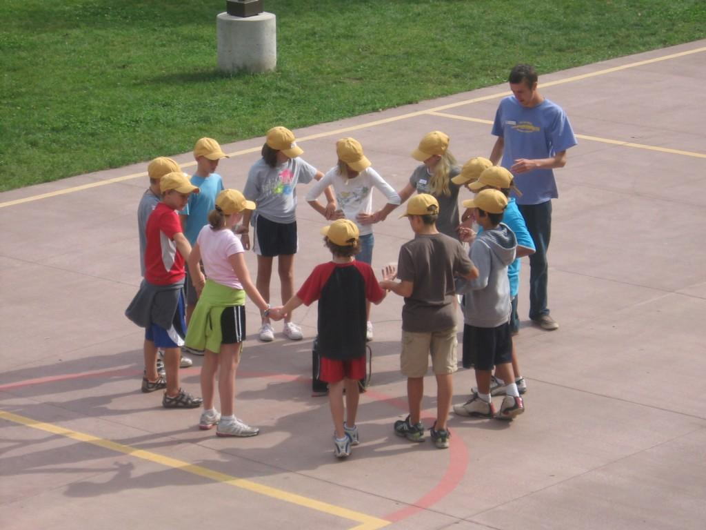 students stand in circle holding hands