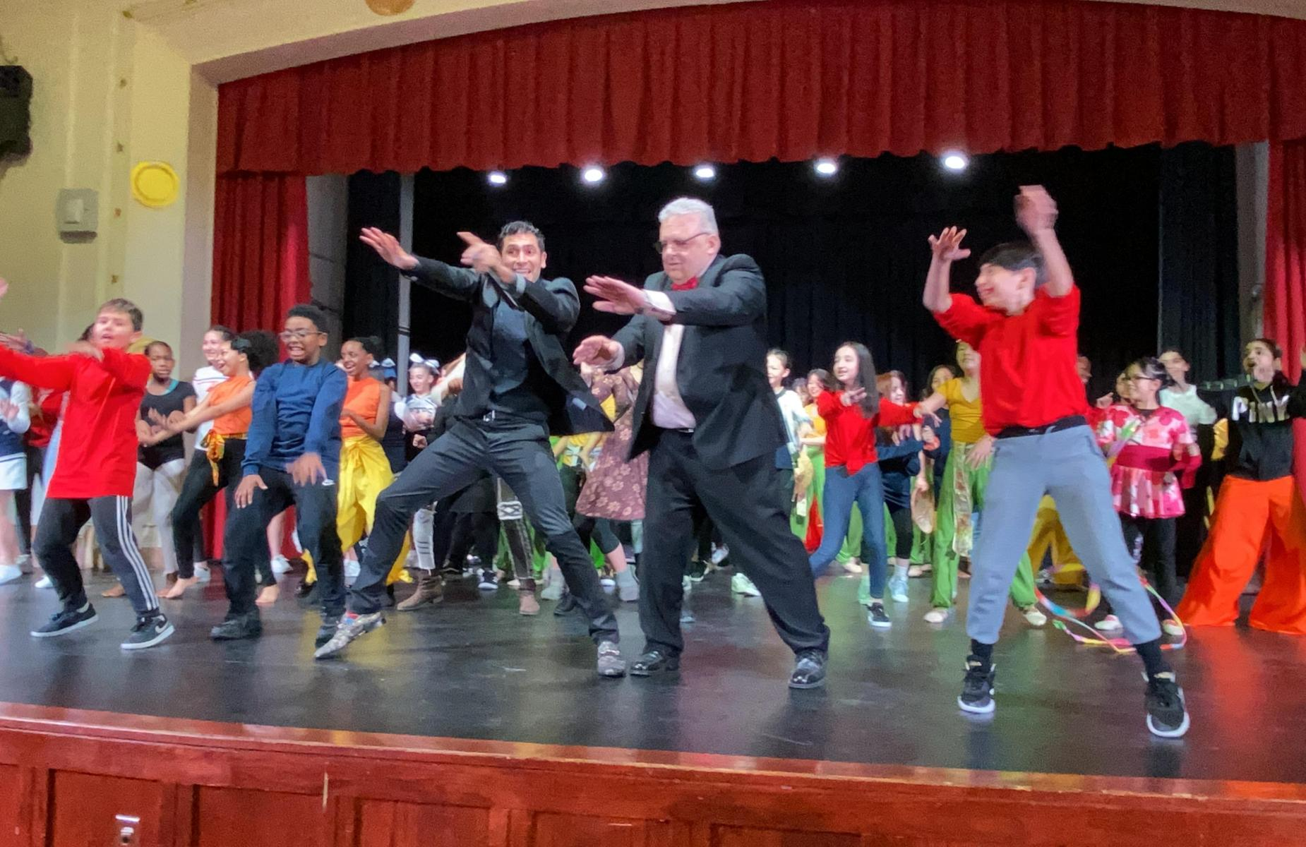 Principal D'Angelo and students dancing together on stage