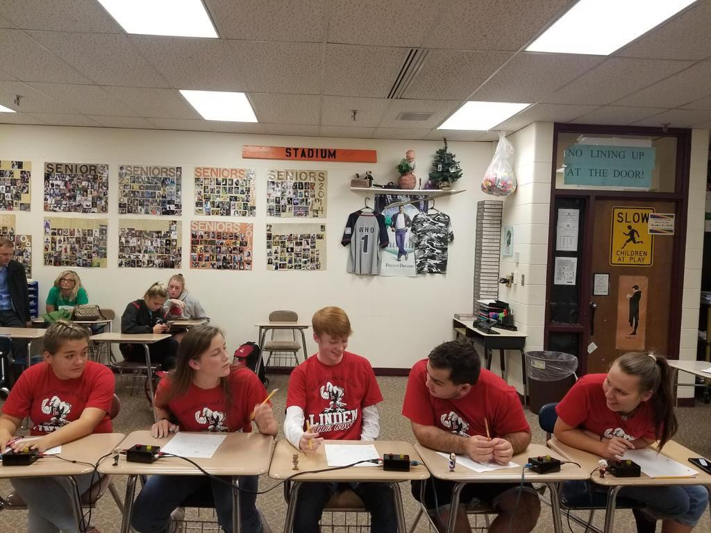 Quiz bowl team sitting in desks and looking at one another