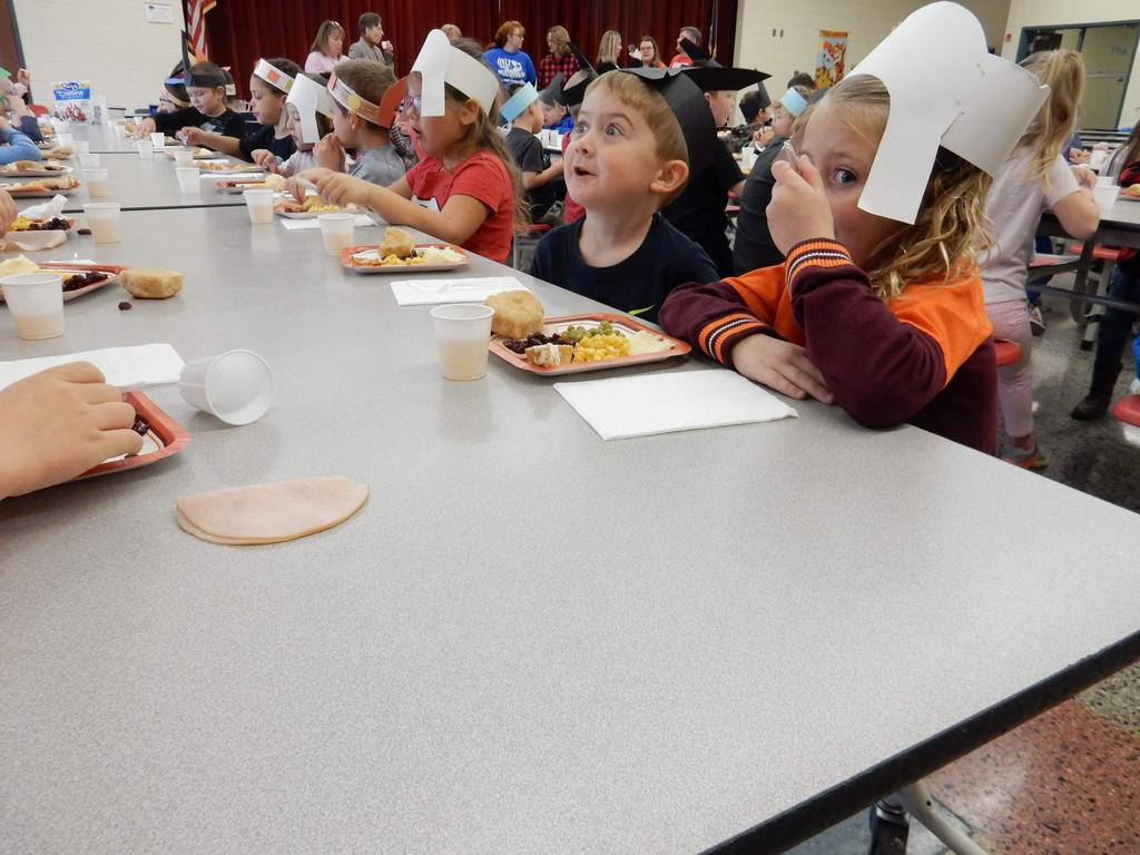 Kindergarten students, dressed as Pilgrims and Native Americans, seated in the cafeteria enjoying a Thanksgiving feast.