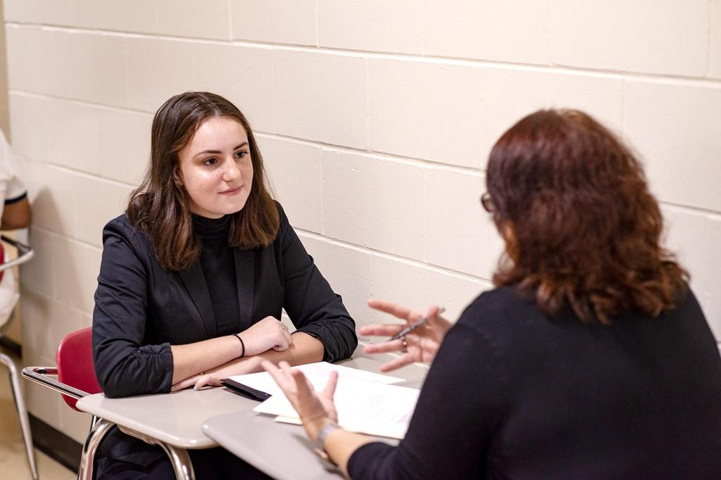 An interviewer gestures with her hands as a student intently looks on