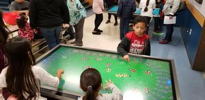 Students playing with an interactive lady bug game
