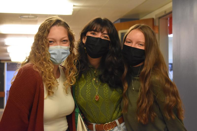 three teen girls smiling from behind face masks