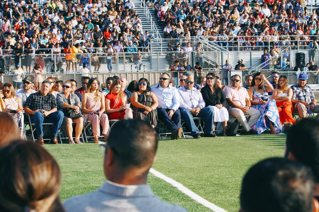 Top Scholar parents sit on field next to grads