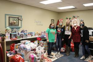 dyer staff involved in the toy drive stand in an office full of donated items