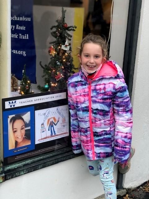 McKinley 2nd grader Cece Lyons in front of Ortho Care with her winning submission showing her teacher, Miss Passananti, teaching Fundations, a comprehensive reading, spelling, and writing program.
