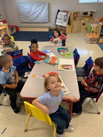 Pre-Kindergarten children sitting around the reading table with their selected books