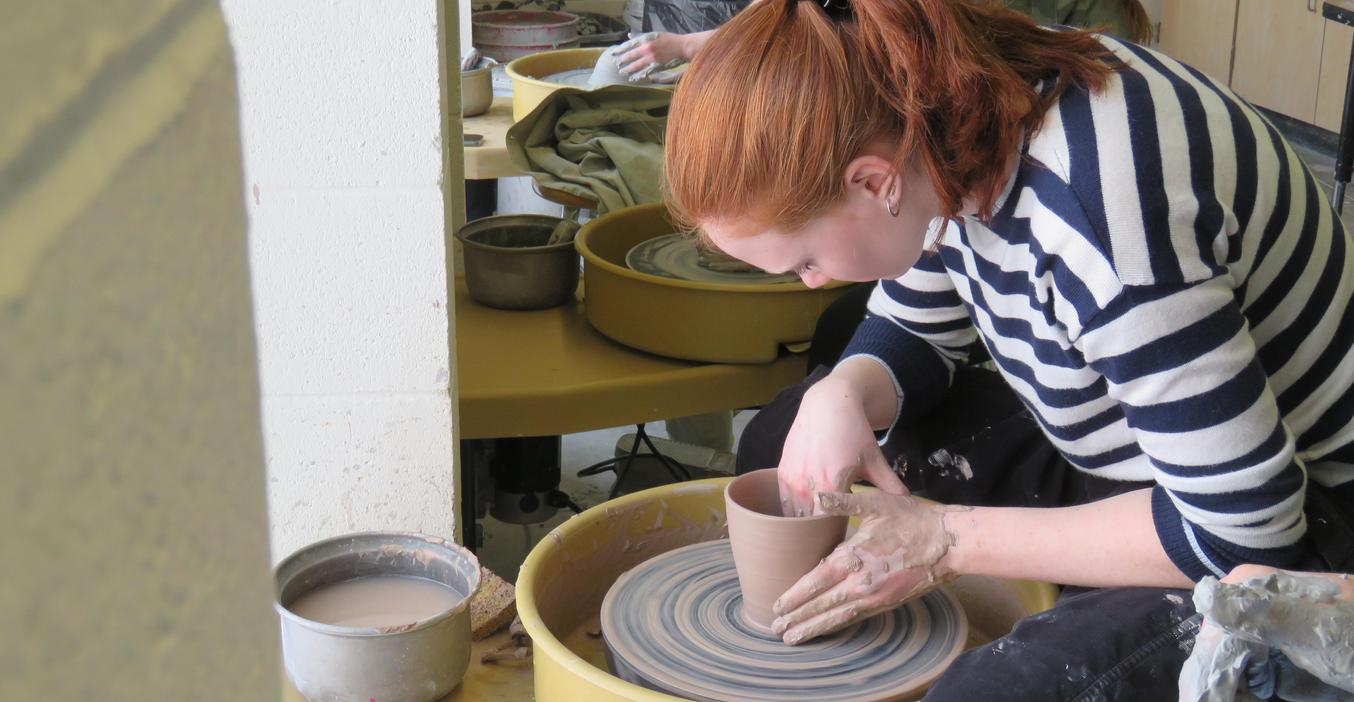 A TKHS art student works on her pottery project.