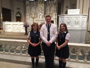 Three OLSH students, two girls and a boy, stand in front of the St. Paul's altar before a concert