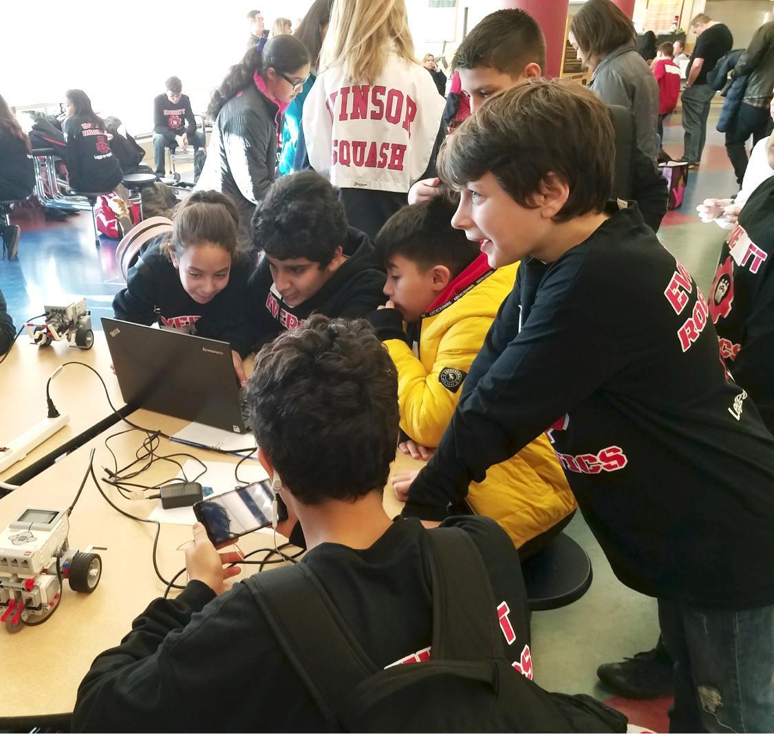 Three students huddle around a laptop