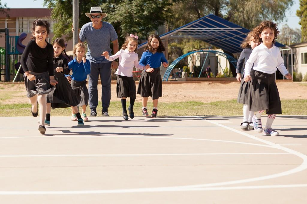 Coach playing with the girls on the basketball court during PE