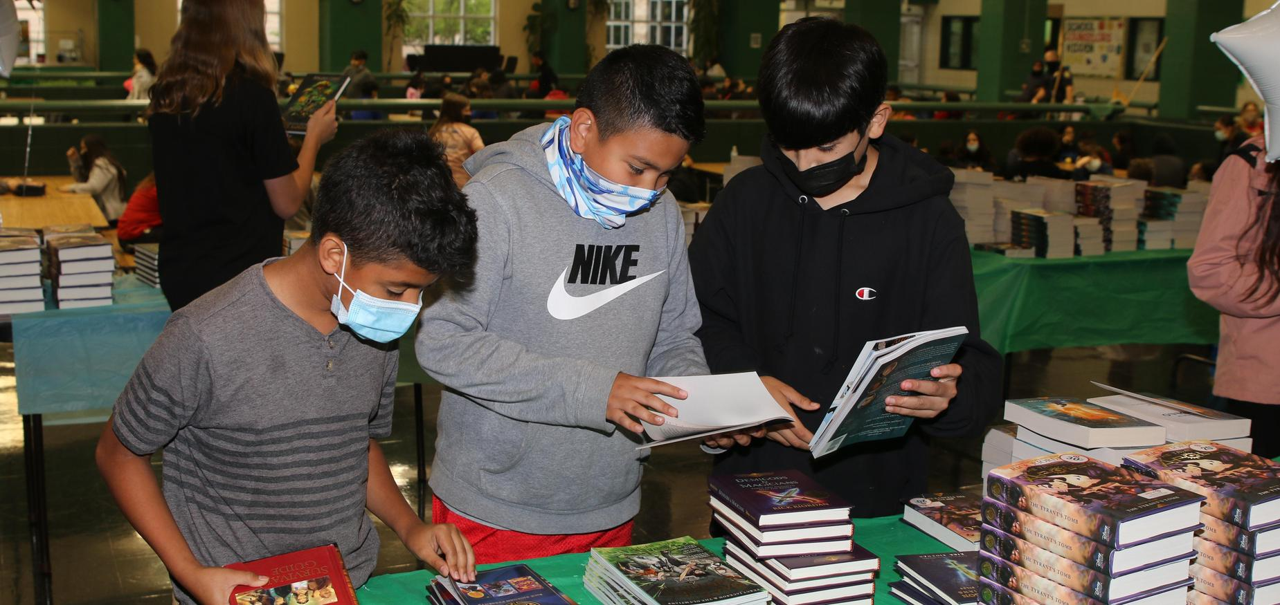 3 boys looking at books.