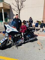 young girl on the ucpd motorcycle with officer next to him