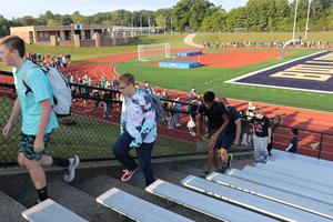 Students walk up a flight of stairs on the bleachers.