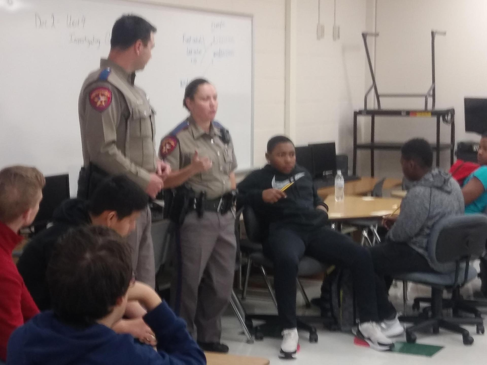 2 uniformed officers talking in front of class