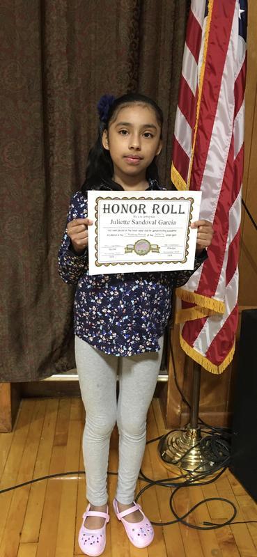 Juliette holding honor roll certificate
