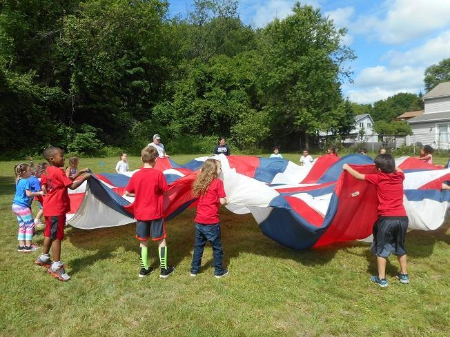 Andrew Avenue students using a parachute on Field Day