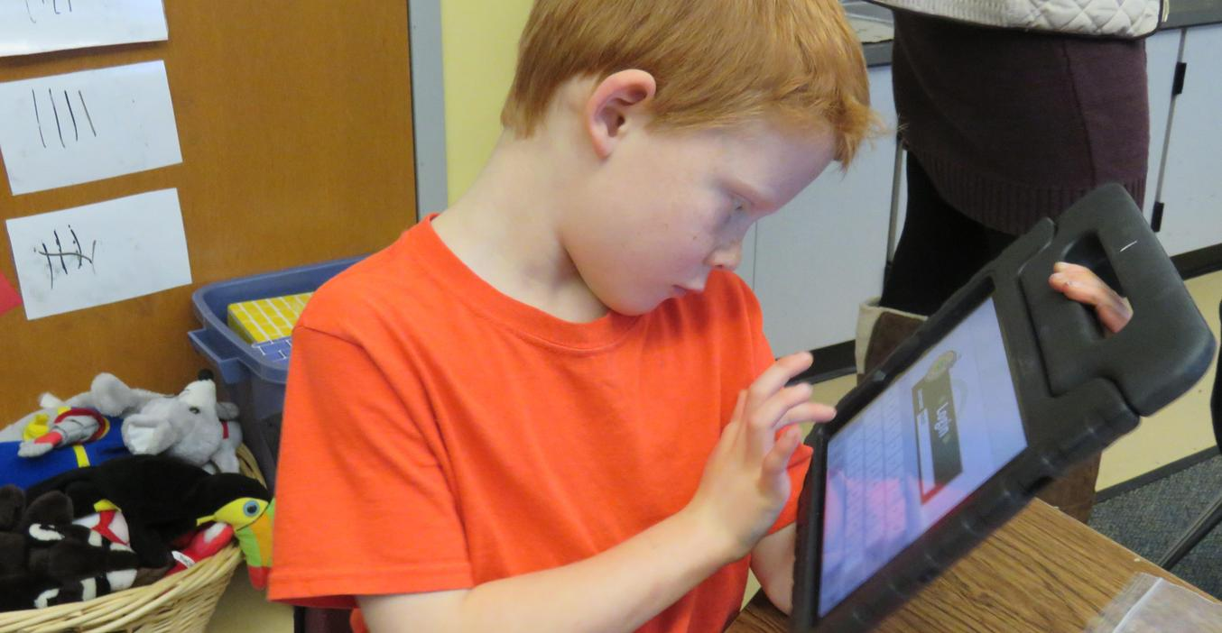 A first grader is busy woking on his iPad.