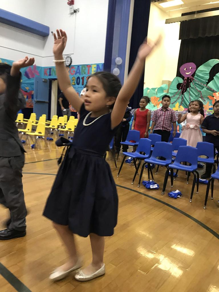 two kids with hands up in the air