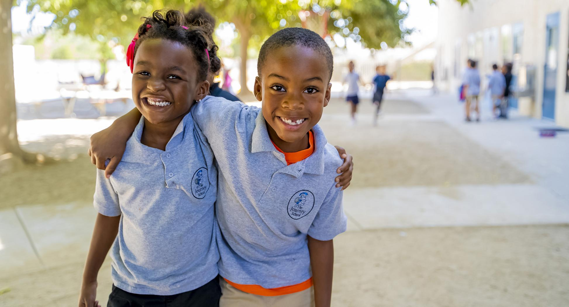 Two students at The Journey School giving a side hug to each other on the school yard, and smiling at the camera. Both students are wearing school uniforms.