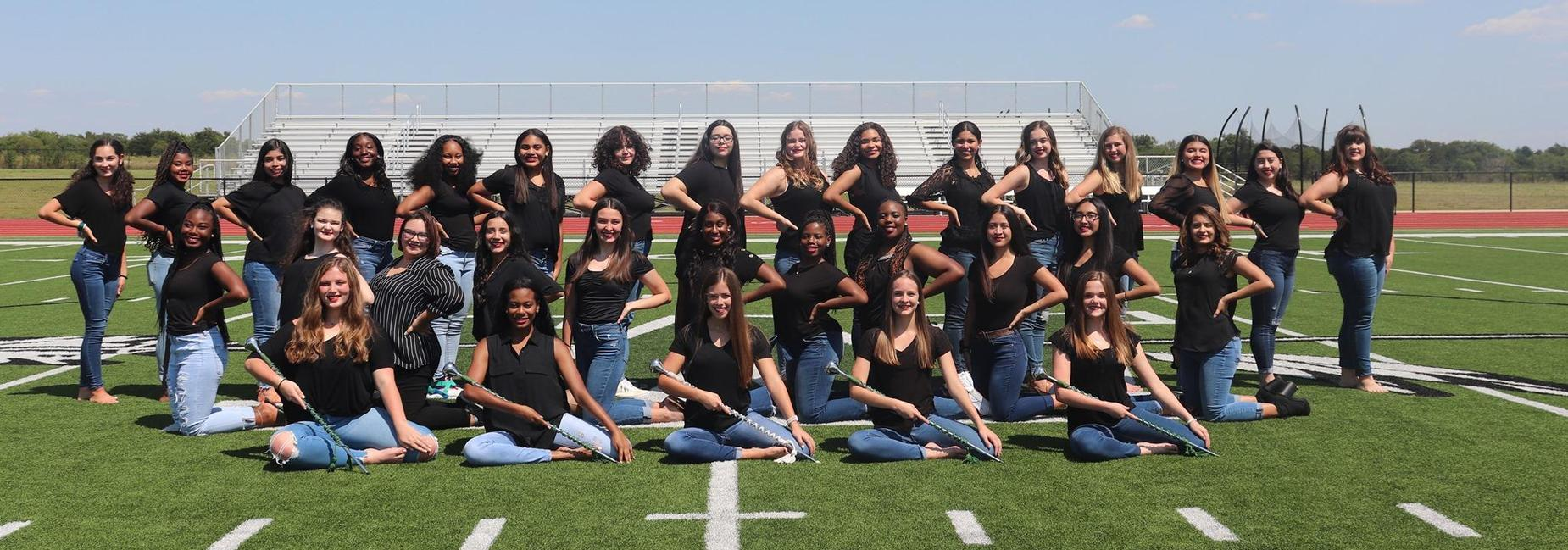 large group of girls posing together on a football field in black shirts & jeans