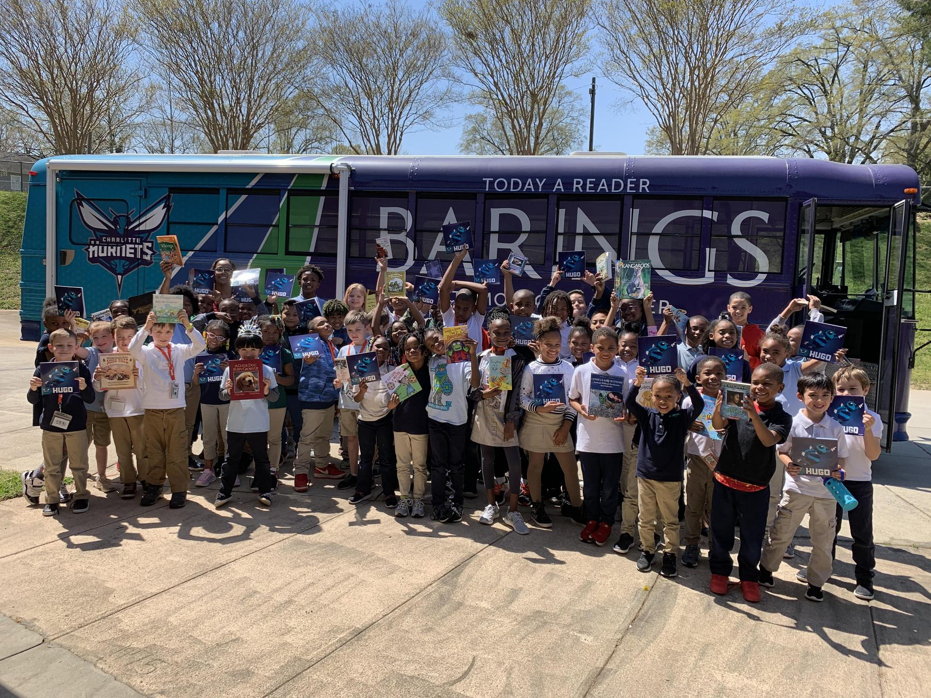 Students with the Barings Book Bus with the free books they were given.